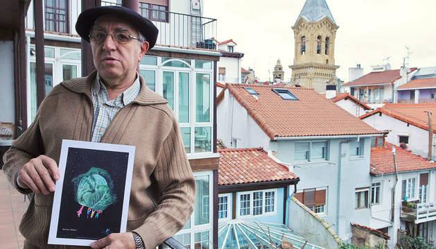 José Javier de la Era, asomado al patio de la sede de Lacarra en Estafeta, sostiene una ilustración de Miren Asiáin.