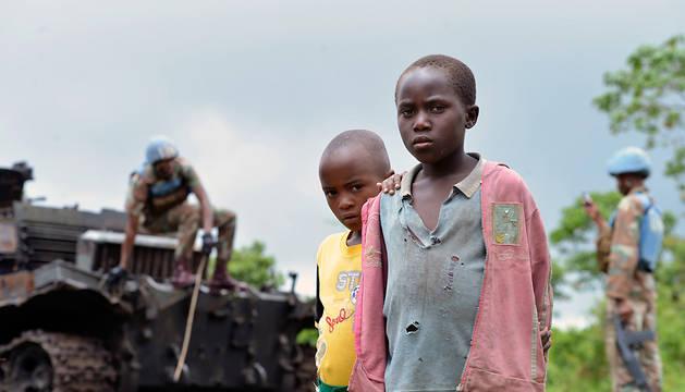 Dos niños congoleses permanecen junto a un carro de combate abandonado por el M23 y que es inspeccionado por cascos azules.