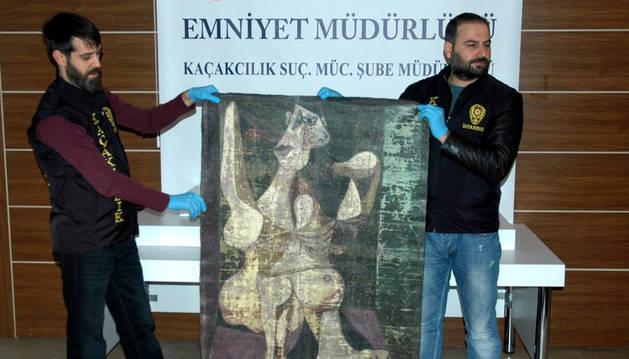 Policías turca con el cuadro incautado, 'Mujer peinándose'.