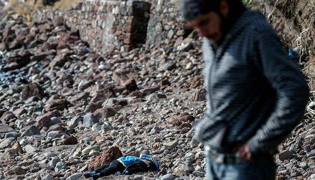 Un hombre pasa junto a uno de los niños que ha muerto en el suceso.