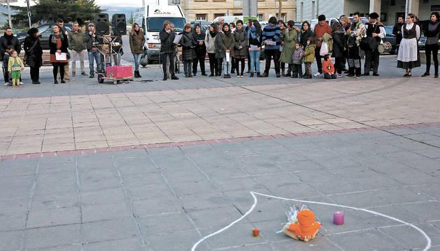 Un grupo de personas en torno a un corazón dibujado con tiza en el pavimento.