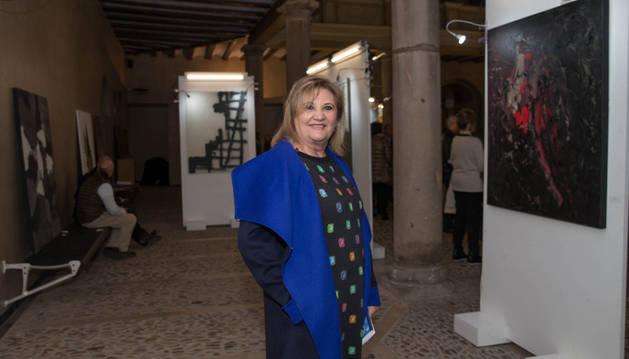 Merche Blasco ante algunas de las obras  de la exposición benéfica ubicada en el patio de la UNED.