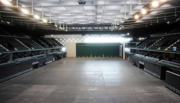 La inmensidad de la pista central del pabellón con el frontón de pelota al fondo.