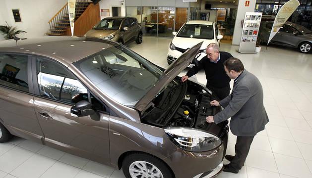 Un hombre estudia un coche en un concesionario.