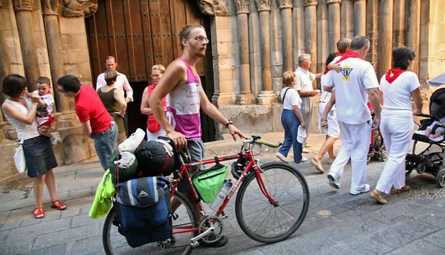 Un turista camina con su bicicleta ante la Puerta del Juicio de la catedral de Tudela.