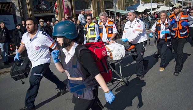 Miembros de los servicios médicos israelíes trasladan a un policía herido, cerca de la Puerta de Damasco en Jerusalén Este.