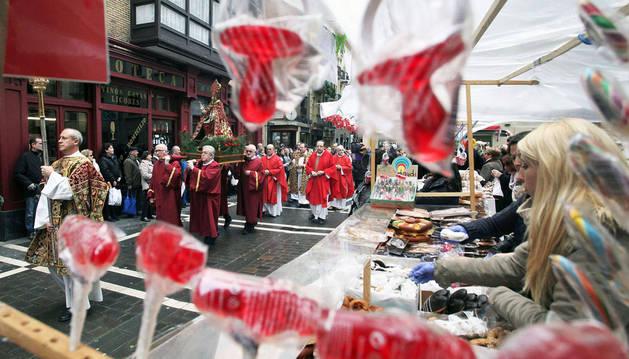 La procesión de San Blas pasa ante el tradicional mercadillo de roscos y dulces.