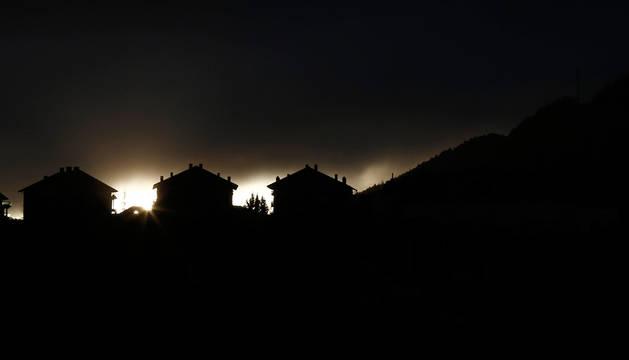 El sol asoma por detrás en unas viviendas en Pamplona.