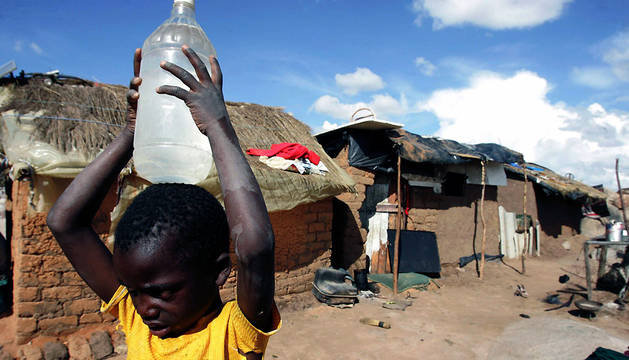 Un niño lleva una garrafa de agua en el suburbio de Epworth, en la capital de Zimbabue, Harare.