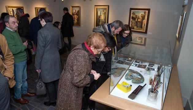 Varias personas contemplan el material de pintura de Monguilot, rodeado de cuadros.