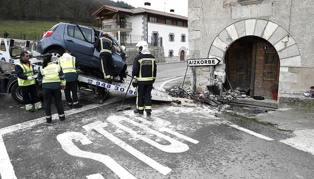 Un bombero retira los restos del vehículo que ha chocado a esta tarde contra una vivienda en el término municipal de Aizcorbe, tras salirse de la vía en el kilómetro 18,900 de la N-240-A. El conductor y único ocupante del vehículo ha muerto en el lugar.