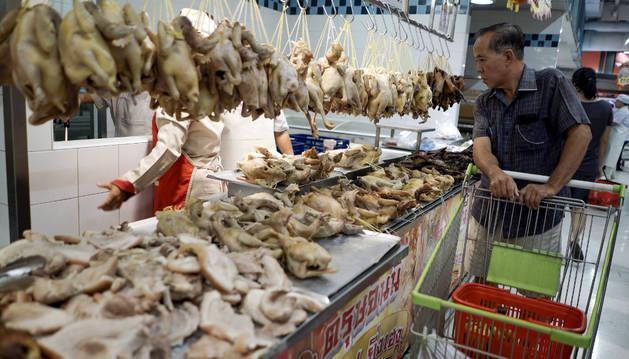 Un hombre mira pollos en un mercado antes del año nuevo lunar chino.