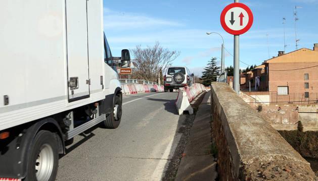 Un camión y un vehículo circulan por el puente  junto a la señal que da paso alternativo.