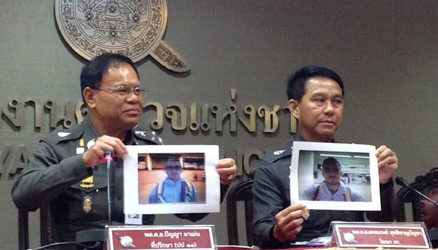 Dos mandos policiales camboyanos muestran fotos del sospechoso.