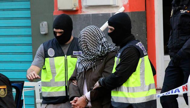 La policía traslada a uno de los detenido, en Ceuta.