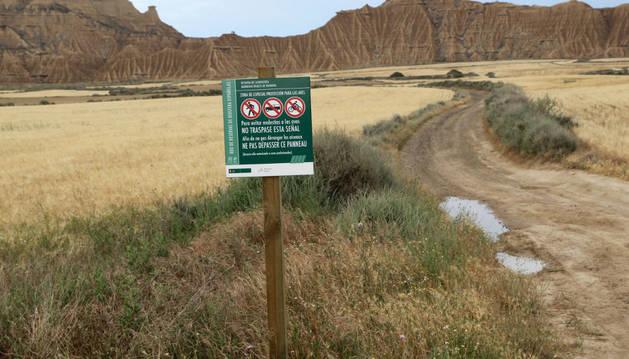 Imagen de una de las señales que informan de la prohibición de paso, con el paraje de Pisquerra al fondo.