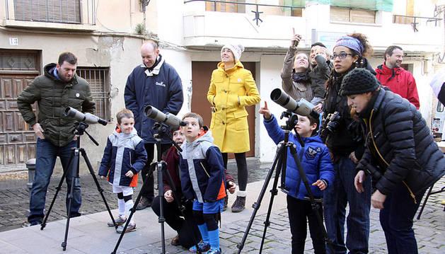 Varios niños observan los nidos de cigüeña a través de los telescopios instalados en Tudela por Gurelur.