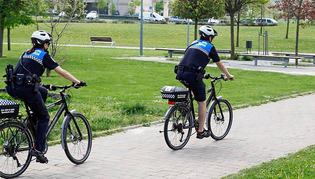 Dos agentes patrullando en bicicleta en uno de los parques de Sarriguren.
