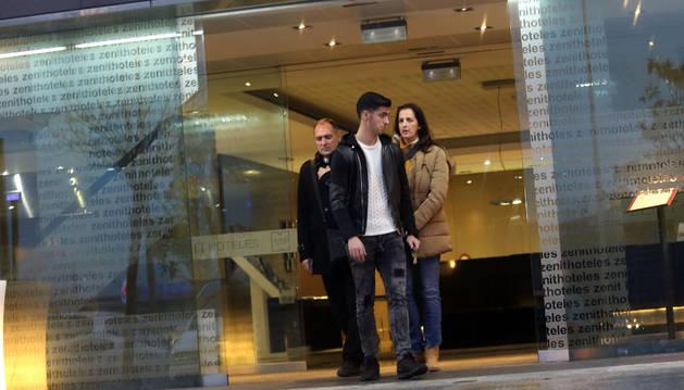Mikel Merino sale de un hotel acompañado por sus padres tras hablar con sus representantes.