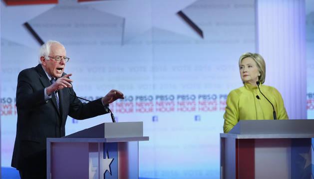 Hillary Clinton escucha una intervención de Bernie Sanders.