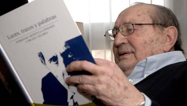 El escritor Miguel Delibes observa el libro 'Luces, trazos y palabras'.