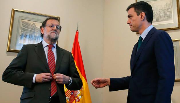 Rajoy, abrochándose la americana mientras Sánchez tiende su brazo para saludarle.