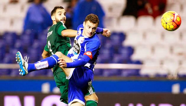 Oriol Riera y Montoya luchan por un balón en Riazor.