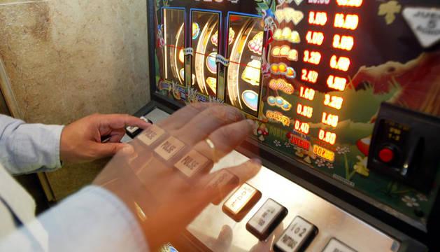 Un hombre juega a una máquina tragaperras.