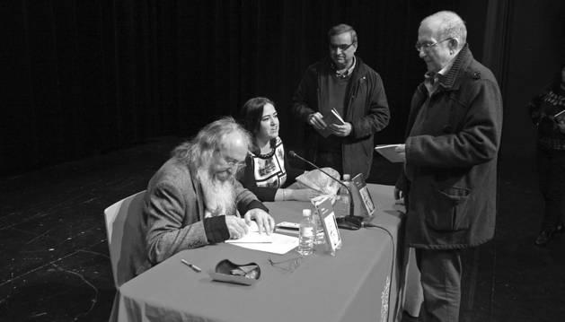 José Luis Allo, a la izquierda, firmando ejemplares de su poemario.