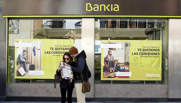 Dos turistas miran un mapa delante de una oficina de Bankia en Madrid.