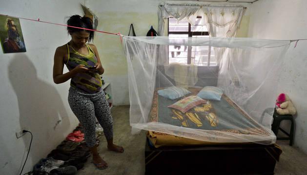 Una mujer embarazada prepara su cama con una mosquitera para combatir al zika en Colombia.