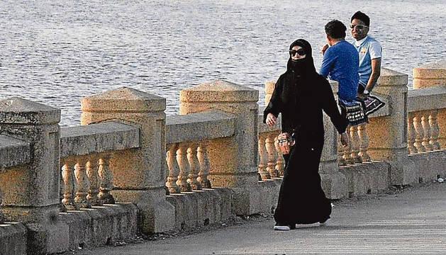 Una mujer saudí camina junto al Mar Rojo.