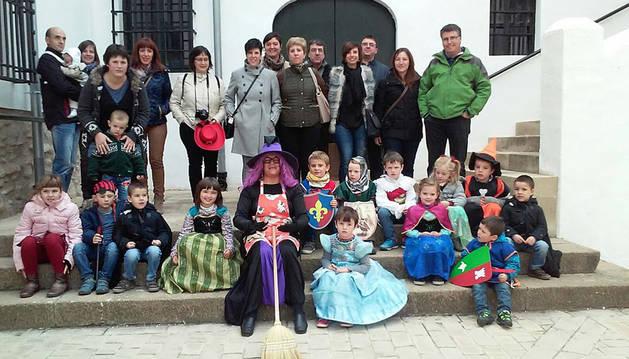 Un grupo de visitantes posa junto a la 'bruja' que les sorprendió en su recorrido por el castillo.
