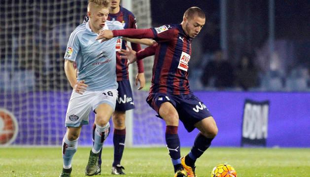 Daniel Wass, del Celta de Vigo, pugna por un balón con el croata Josip Radosevic, del Eibar.