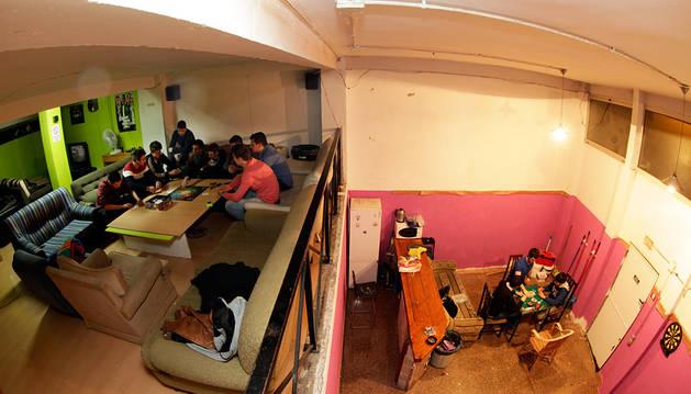 Varios grupos de jóvenes se entretienen con juegos de mesa en el interior de una bajera en Pamplona.