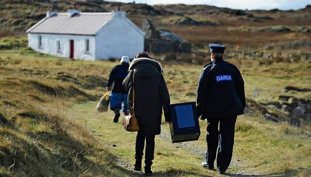 Una agente de la Policía Nacional irlandesa, y Magella Harkin (izda) cargan con una urna al llegar a la isla de Innishre (Irlanda).