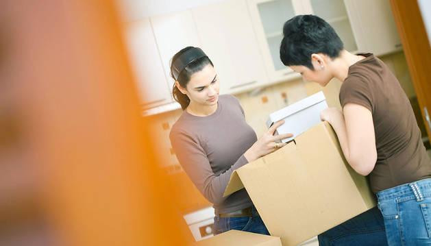 Dos jóvenes hacen la mudanza a su nueva casa.