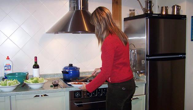 Una mujer, en su casa, utiliza la vitrocerámica para preparar una comida.