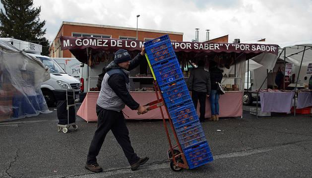 Un vendedor transportando naranjas este domingo para vender en su puesto de Landaben.