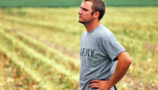 Un joven agricultor mira al horizonte en un campo.