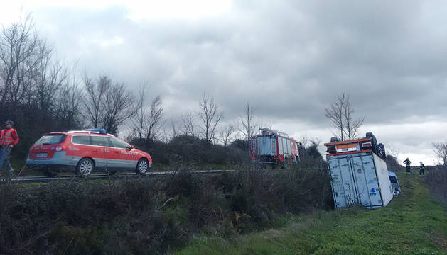 El camión accidentado, volcado tras caer por el talud.