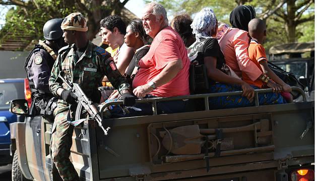 Miembros del Ejército trasladan a varios turistas del hotel atacado en Costa de Marfil.