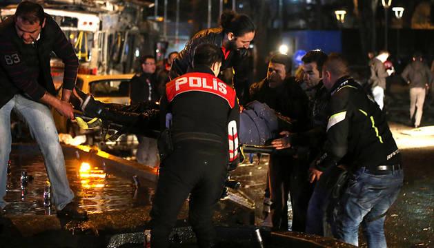 Policías y miembros de los servicios de emergencia trasladan a un herido.