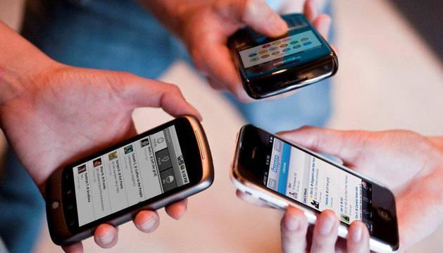 Varias personas miran su teléfono móvil.