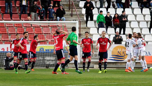 Los jugadores de Osasuna protestan a Saúl Aig Reig al no señalar falta a Nauzet en el 2-0 del Albacete. Al fonto, la plantilla manchega celebra el tanto de Fede Vico.
