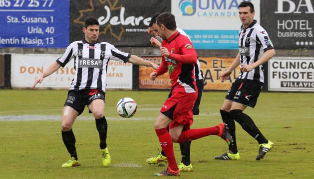 Víctor Bravo, jugador del Tudelano, intenta hacerse ayer con el balón ante tres rivales del Lealtad de Villaviciosa.