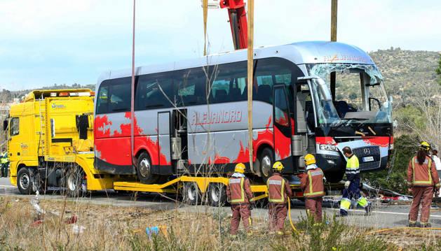 Diversos operarios junto al autocar accidentado.
