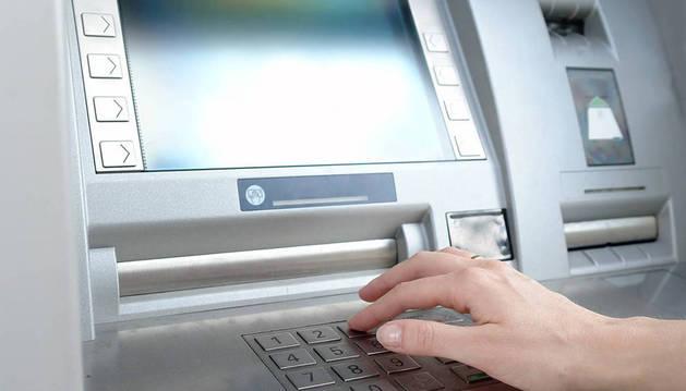 Una persona extrae dinero de un cajero automático.