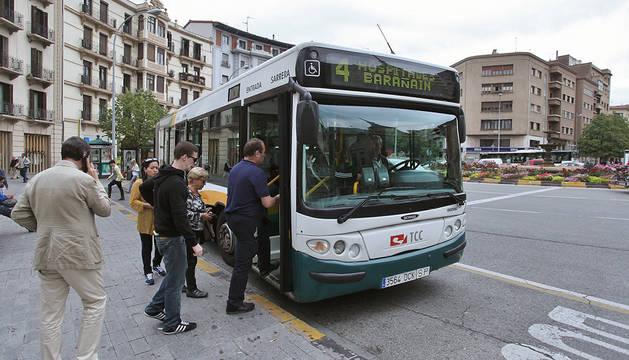 Varios usuarios suben a la línea 4 en la plaza de Merindades.