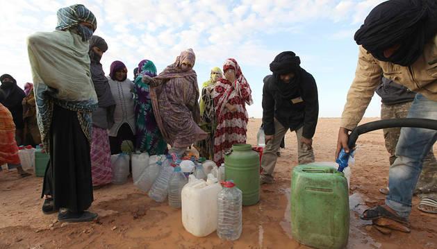 Unas mujeres saharauis hacen cola para recoger agua.